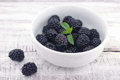 Close up of ripe blackberries in a white ceramic bowl over rusti Stock Image