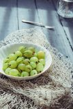 Close up ripe Green fresh gooseberry in ceramic bowl on rustic black wooden kitchen table back lightened by morning light. Farmer. Harvest, local market royalty free stock image