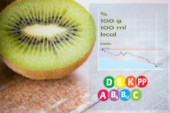 Close up of ripe kiwi slice on table. Fruits, diet, food and objects concept - close up of ripe kiwi slice on table with calories and vitamin chart Stock Photo