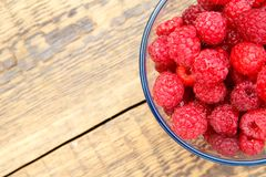 Close up of ripe raspberries in the glass bowl on wooden boards. Freshly picked berries in the garden Stock Photos