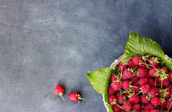 Close up ripe sweet raspberries in bowl on dark background. top view Stock Photos