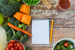 Close up of ripe vegetables and notebook on table Royalty Free Stock Photos
