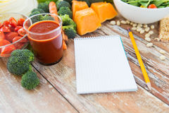 Close up of ripe vegetables and notebook on table Stock Photos