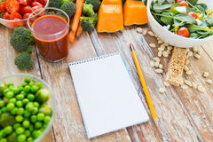 Close up of ripe vegetables and notebook on table Stock Photography