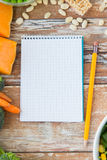 Close up of ripe vegetables and notebook on table Stock Photo