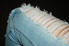 Close-up of a ripped pair of jeans near the knee. Light blue denim jeans with horizontal white rips. A close-up photo showing the leg near the knee. The royalty free stock images