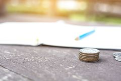 Close up rising coins pile of money coins stack and pencil lied. On a notebook on the wooden table with bokeh of green garden background royalty free stock image