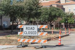 Road closed sign in Downtown Irving, Texas, USA. Close-up road closed sign in Downtown Irving, Texas, USA. Barricade closures, cones with urban buildings in Royalty Free Stock Photo