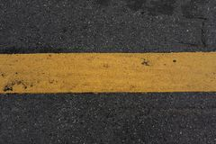 Close-up road texture and yellow stripe. Asphalt road and paint yellow line stock image
