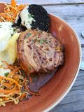 A close up of a roast pork belly dinner. A close up of a roast pork belly with black pudding, mashed potatoes and apple and carrot salad Royalty Free Stock Photo