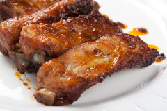 Close up of roast pork ribs. Close up of roast and juicy pork ribs in a white dish stock image
