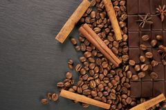 Close-up of roasted arabica coffee beans, dark chocolate bar. And spices anise with cinnamon on dark stone background with copy space Royalty Free Stock Image