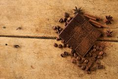 Close-up of roasted arabica coffee beans, dark chocolate bar. And spices anise with cinnamon stick and cocoa powder on old rustic wooden background with copy Stock Photos