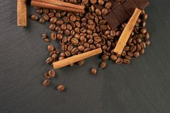 Close-up of roasted arabica coffee beans, dark chocolate bar. And spices anise with cinnamon on dark stone background with copy space Stock Images