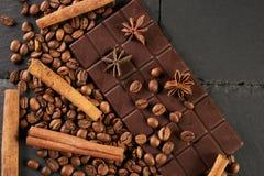 Aromatic set of chocolate bar, arabica coffee beans. Close-up of roasted arabica coffee beans, dark chocolate bar and spices anise with cinnamon on dark stone Stock Photos
