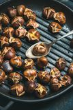 Close-up of roasted chestnuts in grilling pan royalty free stock photos