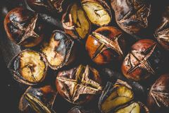 Close up of Roasted chestnuts in iron grilling pan. Royalty Free Stock Image
