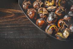 Close-up of Roasted chestnuts in iron grilling pan over rustic wooden table with copy space.  Stock Images