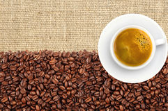 Close-up of roasted coffee beans and coffee cup over linen Royalty Free Stock Image