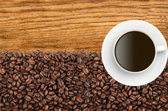 Close-up of roasted coffee beans and coffee cup over wooden Royalty Free Stock Photography