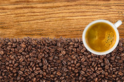 Close-up of roasted coffee beans and cup coffee over wooden Royalty Free Stock Photography