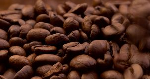 Close-up roasted coffee beans dropping. Close-up of aromatic roasted coffee beans falling down on pile and filling the frame stock footage