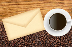 Close-up of roasted coffee beans and envelop and coffee cup Stock Image