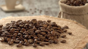 Close-up of roasted coffee beans rotating on burlap. Rustic wooden background. Seamless loopable. Prores 4K. Close-up of roasted coffee beans rotating on gunny stock footage
