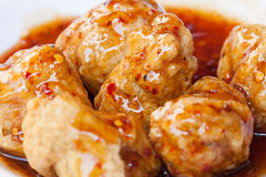 Close up roasted meatballs under meat sauce on white plate Stock Photo