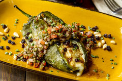 Stuffed Poblano Peppers and Salsa. Close up of roasted Poblano pepper stuffed with melted cheese with fresh salsa garnish sitting on rustic yellow plate shot stock photography
