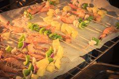 Homemade skewer with delicious grilled shrimps on parchment pape Stock Images