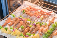Homemade skewer with delicious grilled shrimps on parchment pape Stock Photos