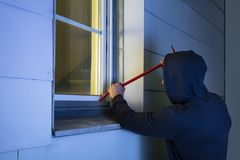 Robber Using The Crowbar To Open The Glass Window. Close-up Of Robber In Hood Using The Red Crowbar To Open The Glass Window Royalty Free Stock Image