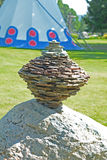 Close up rock cairn sits near an Indian Tee-Pee. Royalty Free Stock Photo