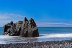 Close-up of rock formation at the coastline against blue sky. Praia Formosa beach in Funchal on Portuguese island of Madeira stock photos