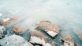 Close up of rocks in a frozen pond. In a cold winter day stock footage