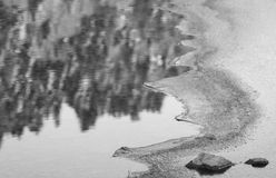 Close up on rocks surrounded by frozen ice plaques in winter season lake in black and white. With reflection Royalty Free Stock Photography