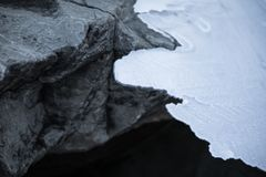 Close up on rocks surrounded by frozen ice plaques in winter season lake. Texture Stock Photography