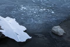 Close up on rocks surrounded by frozen ice plaques in winter season lake. Texture Royalty Free Stock Photography