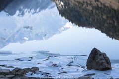 Close up on rocks surrounded by frozen ice plaques in winter season lake. Texture Stock Image