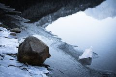 Close up on rocks surrounded by frozen ice plaques in winter season lake. Texture Royalty Free Stock Photos
