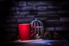 close-up rode Kerstmiskop en de kaars op de vakantielijst Stock Afbeelding
