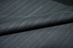 Close up roll black blue shade fabric of suit. Photo shoot by depth of field for object stock photography
