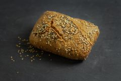 Close-up of a roll bread with seeds on a dark background royalty free stock photo