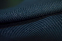Close up roll dark blue fabric with stripe line of suit. Photo shoot by depth of field for object stock photo