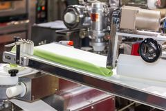 Close up roll dough material for chinese or asian food steamed stuffed buns on automatic belt conveyor of food making machine in. Production line for high stock photo