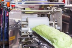 Close up roll dough material for chinese or asian food steamed stuffed buns on belt conveyor of automatic food making machine in. Production line for high stock images