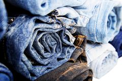 Close up rolled of blue jeans pants, dark blue denim trousers showing texture on white Royalty Free Stock Image