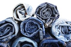 Close up rolled of blue jeans pants, dark blue denim trousers showing texture on white Stock Image