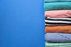 Rolled colorful clothes on blue background Stock Images